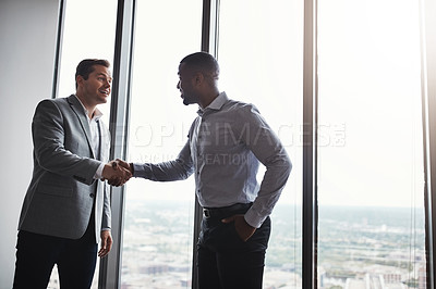 Buy stock photo Low angle shot of two corporate businessmen shaking hands during a meeting in the boardroom
