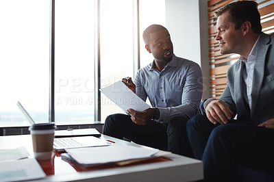 Buy stock photo Shot of two businessmen going through paperwork in an office