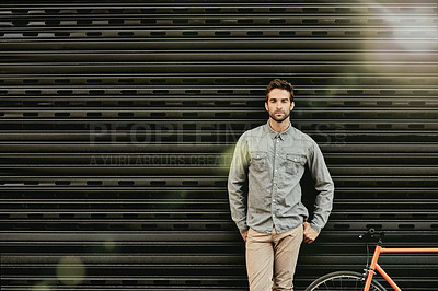 Buy stock photo Shot of a handsome young man against an urban backdrop