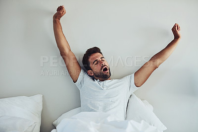 Buy stock photo Shot of a tired young man waking up after a good night's sleep while putting is arms in the air and yawning