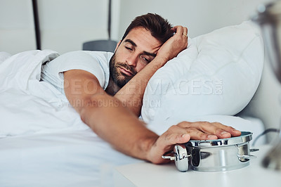 Buy stock photo Shot of a tired young man sleeping is his bed while holding a alarm clock after getting woken up from it