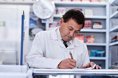 Buy stock photo Shot of a male pharmacist working in a pharmacy
