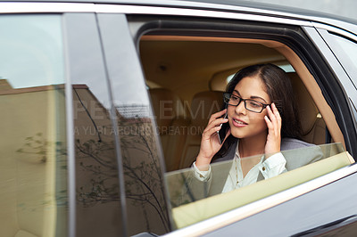 Buy stock photo Shot of a young businesswoman talking on her cellphone while sitting in the backseat of a car