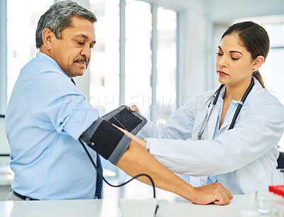 Buy stock photo Shot of a doctor checking a patient's blood pressure in a hospital
