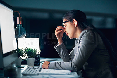 Buy stock photo Shot of a young businesswoman experiencing a headache in the office