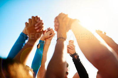 Buy stock photo Shot of a group of unrecognizable people holding hands together in the air