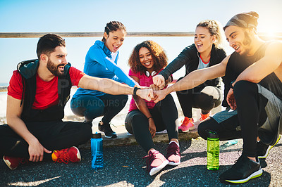 Buy stock photo Shot of a group of young cheerful friends forming a huddle after a fitness exercise outside during the day