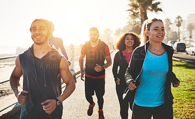 Buy stock photo Shot of a fitness group out running on the promenade