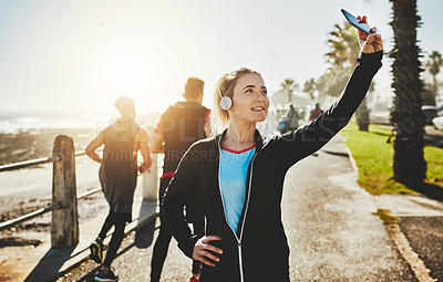 Buy stock photo Cropped shot of a sporty young woman taking a selfie while out on the promenade