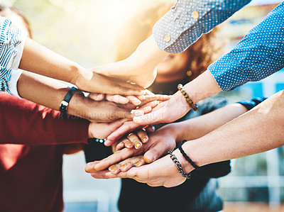 Buy stock photo Cropped shot of an unrecognizable group of college friends standing outside with their hands in a huddle