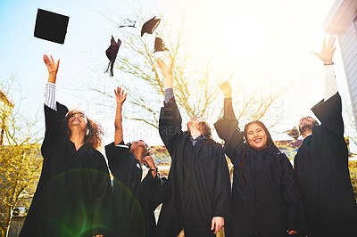 Buy stock photo Cropped shot of a group of students throwing their caps into the air after graduating