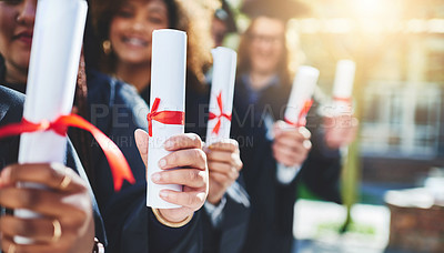Buy stock photo Cropped shot of a group of students holding their diplomas on graduation day