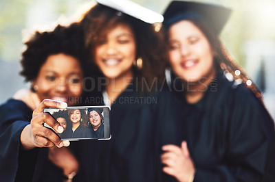 Buy stock photo Cropped shot of three students taking a selfie on graduation day