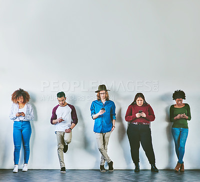 Buy stock photo Studio shot of a group of young people standing against a wall and using their mobile phones