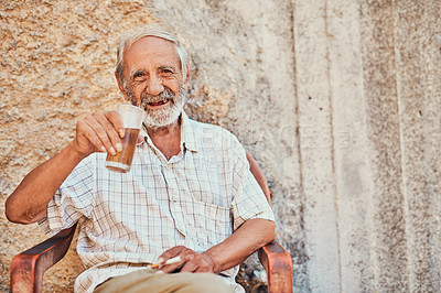 Buy stock photo Portrait of a senior man drinking and smoking outside on the sidewalk of an ancient city