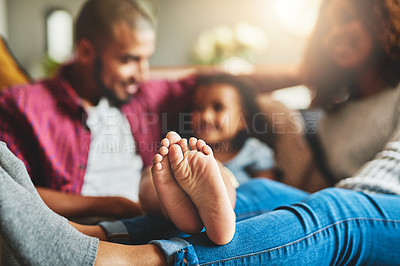 Buy stock photo Cropped shot of a family of three relaxing together on the sofa at home