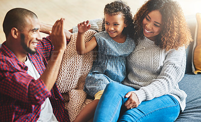 Buy stock photo Shot of an adorable little girl and her parents playing together on the sofa at home