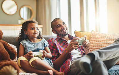 Buy stock photo Shot of an adorable little girl and her father playing video games together on the sofa at home