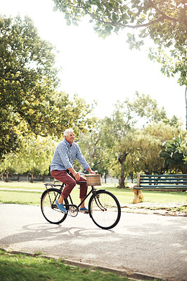 Buy stock photo Shot of a senior man going for a bicycle ride in the park