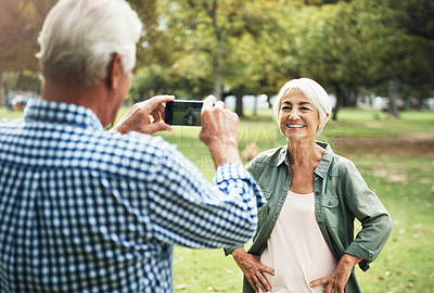 Buy stock photo Shot of a senior man taking photographs of his wife on a mobile phone in the park