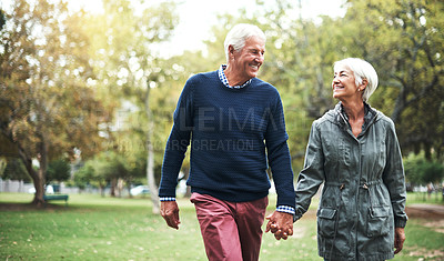 Buy stock photo Cropped shot of a mature couple walking hand in hand through the park