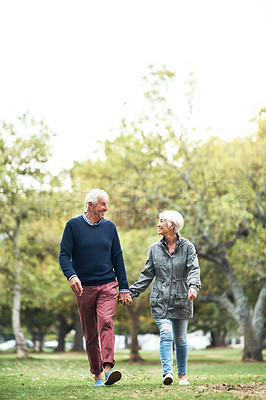 Buy stock photo Shot of a mature couple walking hand in hand through the park