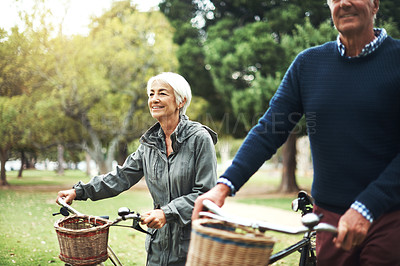Buy stock photo Shot of a mature couple pushing their bicycles while walking through the park