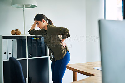Buy stock photo Shot of a young businesswoman suffering with back pain in an office