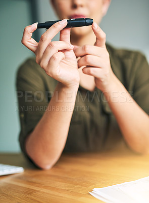 Buy stock photo Closeup shot of an unidentifiable businesswoman testing her blood sugar level in an office