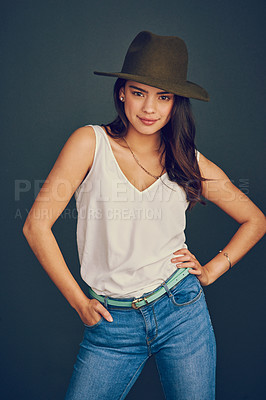 Buy stock photo Studio shot of an attractive young woman wearing a hat and posing while standing against a dark background