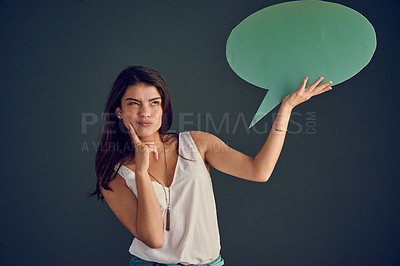 Buy stock photo Studio shot of a carefree young woman holding up a speech bubble while contemplating and standing against a dark background