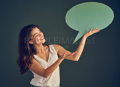 Buy stock photo Studio shot of a cheerful young woman holding up a speech bubble while standing against a dark background