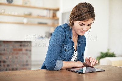Buy stock photo Cropped shot of an attractive young woman using her tablet while sitting in the kitchen at home