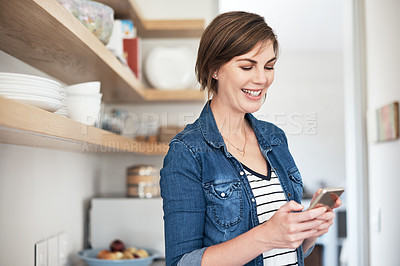Buy stock photo Cropped shot of an attractive young woman using her cellphone while standing in the kitchen at home