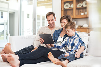 Buy stock photo Full length shot of a young family of three using a tablet while sitting on their sofa at home