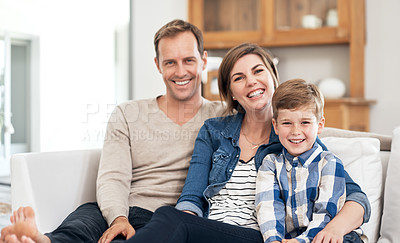Buy stock photo Cropped portrait of a young family of three using a tablet while sitting on their sofa at home
