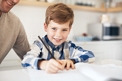 Buy stock photo Cropped portrait of an adorable little boy doing his homework while sitting in the kitchen with his father