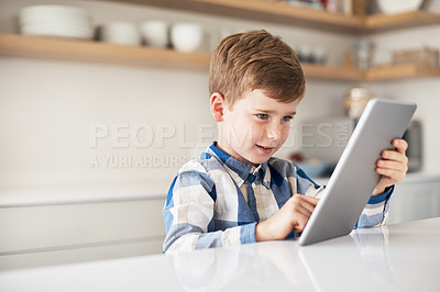 Buy stock photo Cropped shot of an adorable little boy using his tablet while sitting in the kitchen at home
