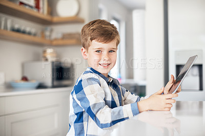 Buy stock photo Cropped portrait of an adorable little boy using his tablet while sitting in the kitchen at home