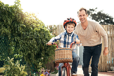 Buy stock photo Cropped portrait of an adorable little boy learning how to ride a bike with his father outside