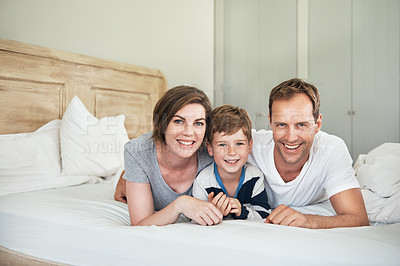 Buy stock photo Shot of a young boy lying in bed with his parents
