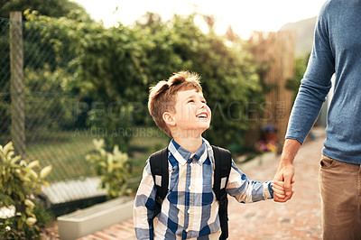 Buy stock photo Shot of a young boy carrying his backpack while walking with his father