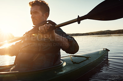 Buy stock photo Shot of a young man kayaking on a lake outdoors