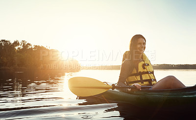 Buy stock photo Shot of a beautiful young woman kayaking on a lake outdoors