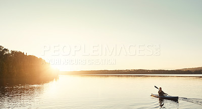 Buy stock photo Shot of a man kayaking on a lake outdoors