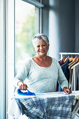 Buy stock photo Portrait of a mature woman ironing clothing at home