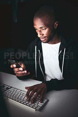 Buy stock photo High angle shot of a young man using his cellphone while working late in the office