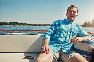 Buy stock photo Shot of a handsome young man spending the day on a private yacht