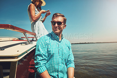 Buy stock photo Shot of a young couple going on a boat ride