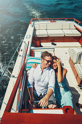 Buy stock photo High angle shot of an affectionate young couple sailing on the open seas in their yacht
